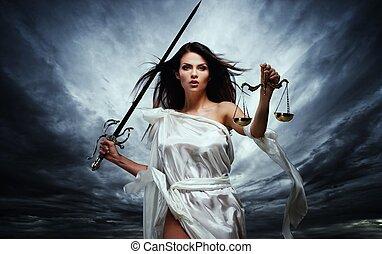 Femida, Göttin der Gerechtigkeit, mit Waagen und Schwert gegen den dramatischen stürmischen Himmel.