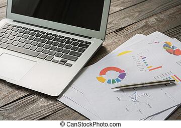 Finanzdiagramme auf dem Tisch mit Laptop.
