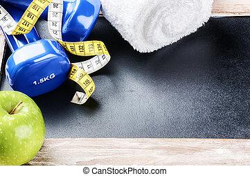 Fitness-Konzept mit Dumbellen und grünem Apfel