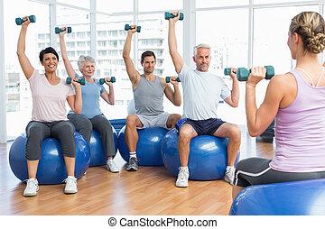 Fitness-Kurs mit Dummern, die auf Übungsbällen sitzen.