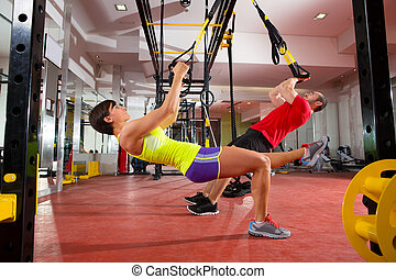 Fitness TRX Trainingsübungen bei Frau und Mann.