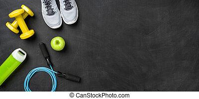 Fitnessgeräte im dunklen Hintergrund mit Kopierraum.