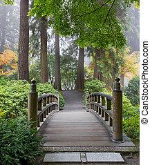 Foggy Morning an der Holzfußbrücke im japanischen Garten