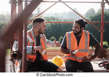 Fröhliche Arbeiter in der Baustelle während der Mittagspause