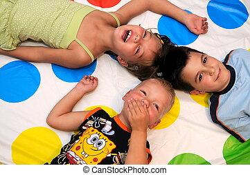 Fröhliche drei Kinder, die zusammen spielen