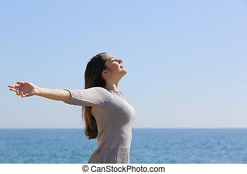Fröhliche Frau, die tief Luft atmen und die Arme am Strand erheben.
