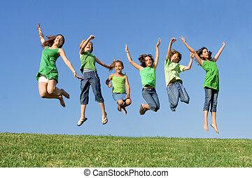 Fröhliche Gruppe gemischter Rassenkinder im Sommercamp oder Schulspringen