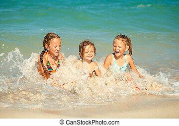 Fröhliche Kinder, die tagsüber am Strand spielen
