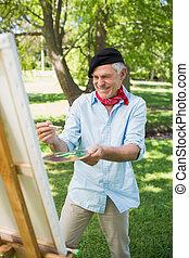 Fröhliche reife Männermalerei im Park.