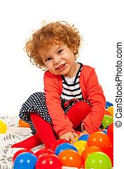 Fröhliches Kleinkind mit bunten Bällen