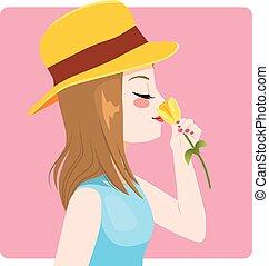 Frühlingsfrau riecht gelbe Tulpe.