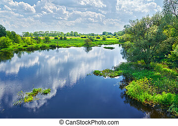 Frühlingslandschaft mit Narew River und Wolken am Himmel