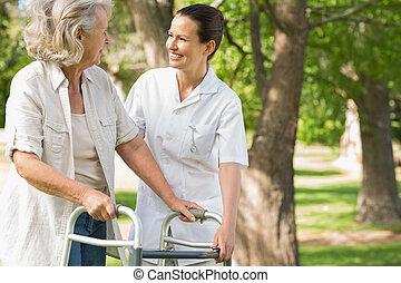 Frau assistiert reife Frau mit Walker im Park.