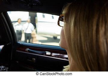 Frau in Limousine am Flughafenterminal.
