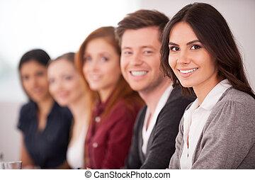 frau, sie, sitzen, fotoapperat, leute, junger, seminar., während, andere, attraktive, hinten, lächeln, reihe