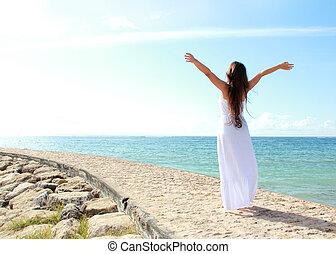 Frauen entspannen sich am Strand mit offenen Armen und genießen ihre Freiheit