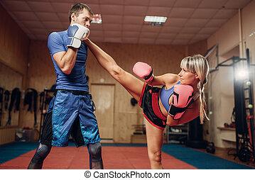 Frauen Kickboxer mit männlichem Personal Trainer