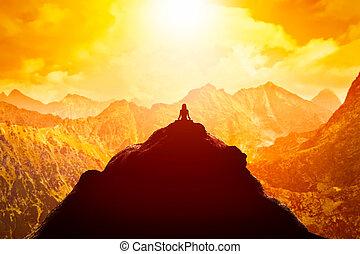 Frauen meditieren in sitzend Yoga Position auf dem Gipfel eines Berges über Wolken bei Sonnenuntergang.