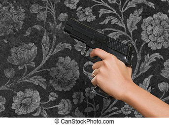 Frauenhand mit einer Waffe