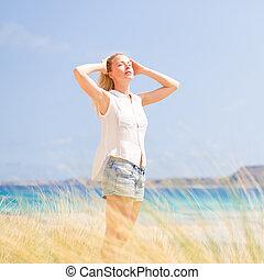 Freie glückliche Frau, die Sonne im Urlaub genießt.