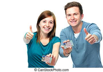 Frohe Teenager, die ihren Führerschein zeigen.
