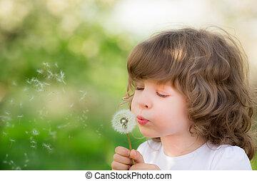 Frohes Kind, das Dandelion bläst.