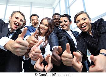Frohes multiethnisches Geschäftsteam mit Daumen im Büro