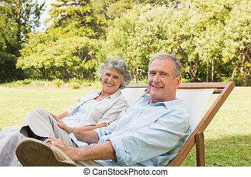 Frohes reifes Paar, das auf der Sonne sitzt.