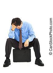 Frustrierter Geschäftsmann sitzt auf dem Aktenkoffer