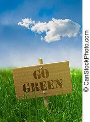 Gehen Sie einen grünen Text auf einem Karton mit Grasblauem Himmel