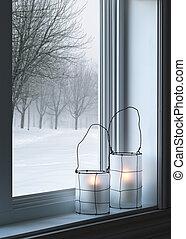 Gemütliche Laternen und Winterlandschaft durchs Fenster gesehen