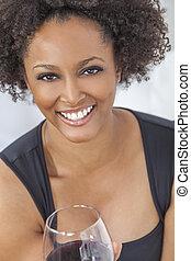 Gemischte Rassenafrikanische Amerikanerin trinken Rotwein.