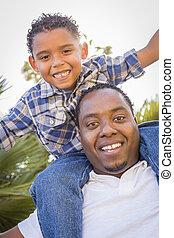 Gemischter Rennvater und Sohn spielen Huckepack im Park