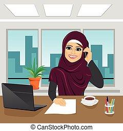 Geschäfts-Arab Frau mit Laptop im Büro mit Hijab Gespräch am Telefon.
