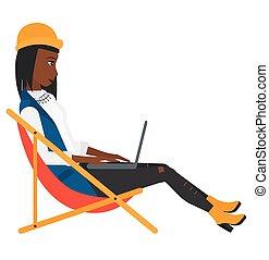 Geschäftsfrau sitzt in Chaise Lounge mit Laptop.