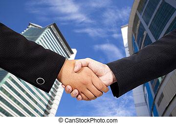 Geschäftsleute schütteln Hände gegen den blauen Himmel und das moderne Gebäude