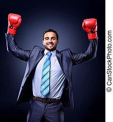 Geschäftsmann in einem Anzug und Boxhandschuhen, feiern einen Sieg, isoliert im schwarzen Hintergrund