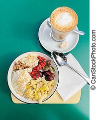 Gesundes Frühstück mit frischem Obst und flachem weißen Kaffee.