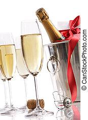 Gläser mit Champagner in Eiskübel und Geschenk