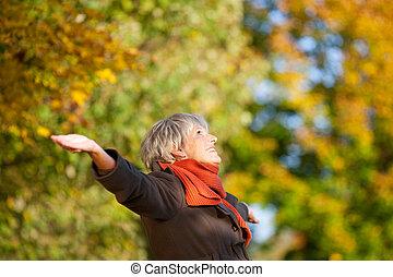 Glückliche ältere Frau genießt die Natur im Park