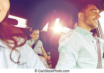 Glückliche Familie mit kleinen Kindern, die im Auto fahren.