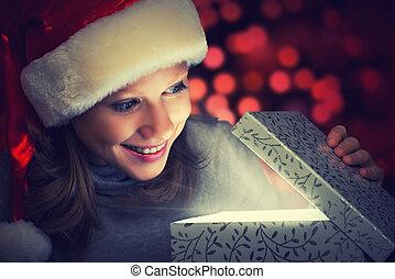 Glückliche Frau mit Weihnachtsmütze öffnet die Zauberkiste