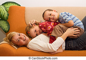 Glückliche Frau und Kinder haben drinnen Spaß