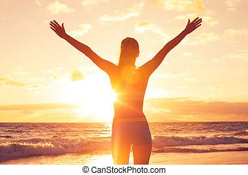 Glückliche freie Frau bei Sonnenuntergang am Strand.