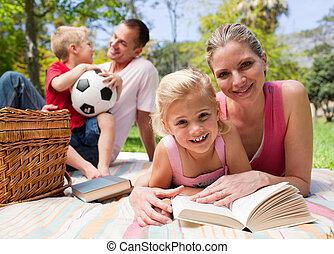 Glückliche junge Familie, die ein Picknick genießt