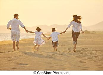 Glückliche junge Familie, viel Spaß am Strand bei Sonnenuntergang