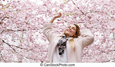 Glückliche junge Frau genießt frische Luft im Frühlingsblütenpark