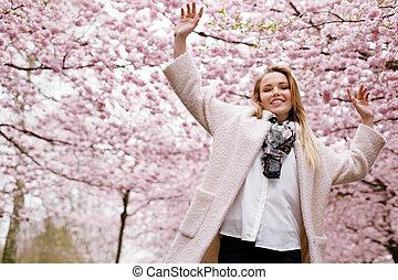 Glückliche junge Frau im Frühlingsblütenpark.