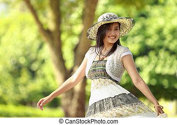 Glückliche junge Frau lächelt im Park