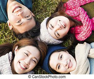 Glückliche junge Gruppe mit Winterkleidung auf dem Rasen.